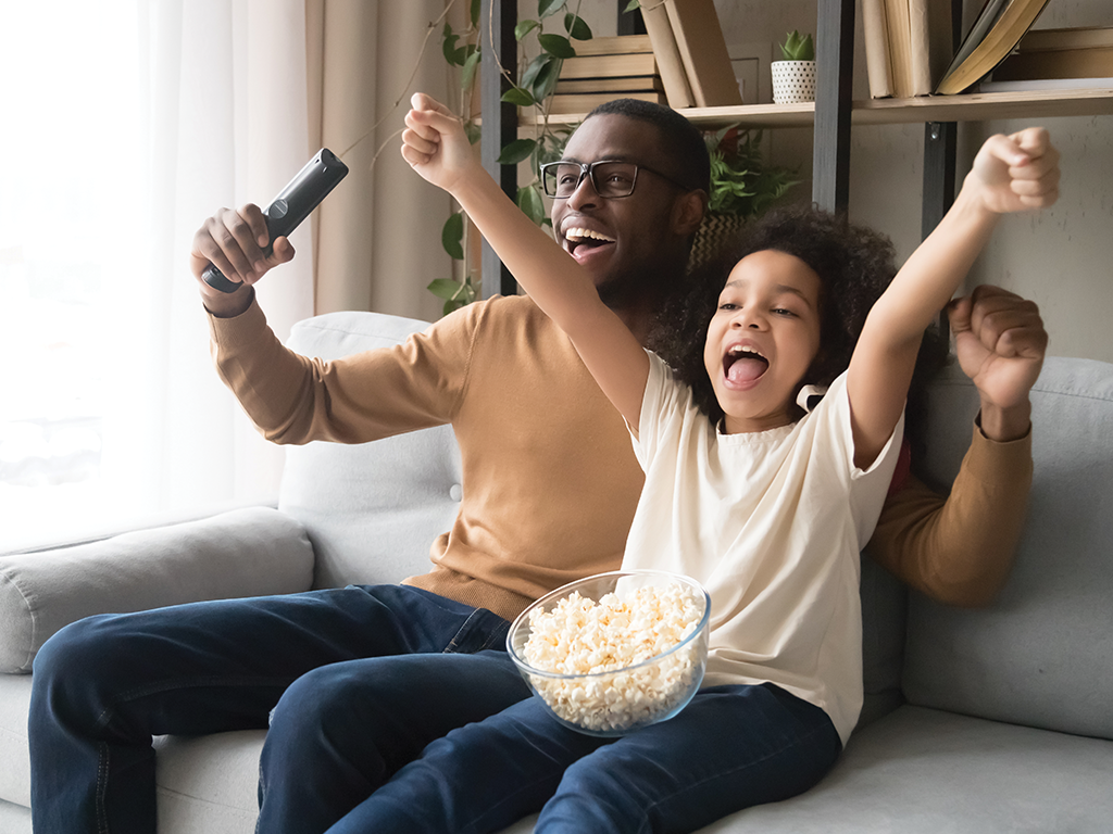 father and child cheering on the sofa